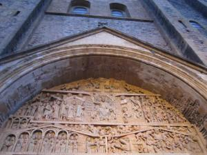 Tympanum of the Last Judgement, which artistically drapes over the entrance of the church in Conques